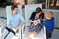 Parents with son on patio, mother playing ukelele