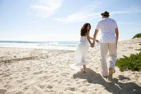 Couple dressed in white walking on sandy beach
