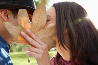 Young couple kissing behind autumn leaf