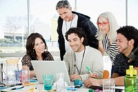 Group of people looking at laptop in office (thumbnail)