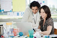 Man and woman looking at laptop on office