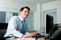 Office worker sitting at desk, smiling