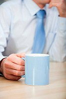 Office worker holding mug, close up
