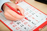 Office worker marking calendar with red pen (thumbnail)
