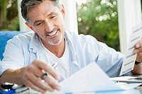 Smiling man doing paperwork