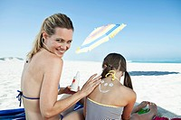 Happy mother applying suntan lotion on her daughter 10-12 back on beach (thumbnail)