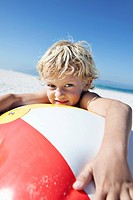 Portrait of young boy 5_6 holding beach ball on beach