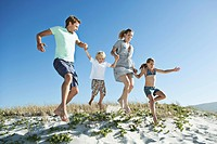 Family with two children 7_9, 10_12 jumping on sand dune and holding hands