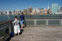 FATHER AND SON FISHING IN THE EAST RIVER FROM A PIER IN QUEENS, LEISURE, NEW YORK, UNITED STATES OF AMERICA, USA