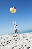 Girl 10_12 throwing beach ball, low angle view