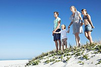 Family with two children 7_9, 10_12 standing on sand dune and holding hands