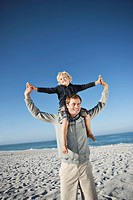 Father standing on beach and carrying son 5_6 on shoulders