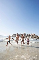 Family with two children 5_6, 10_12 running on beach and holding hands