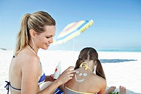 Woman applying sun cream on daughter´s 10_12 back