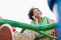 Boy at playground talking on mobile phone