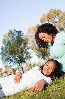 Mother with daughter 13_15 resting on grass in park