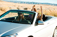 Three women driving in convertible car