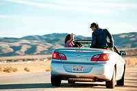 Young man and woman in convertible car