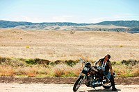 Man on motorcycle parked at roadside
