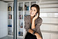 Smiling woman talking on cell phone in office