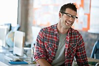 Portrait of smiling man sitting on desk in office