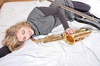 Blonde young woman with a musical instrument at home