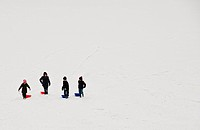 England, Essex, Basildon. Children walking with their sleds up a snow covered slope.