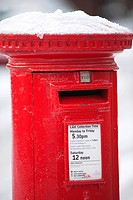 England, London, Merton. Snow on the top of a traditional red post box in South London.
