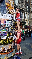 Scotland, City of Edinburgh, Edinburgh. Performers sticking a poster to a column in the High Street advertising shows on at the Fringe at the Edinburg...