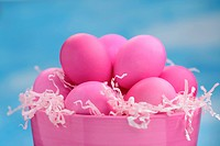 Pink Easter eggs on Easter grass in bowl