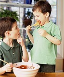 Two boys licking chocolate cake mixture