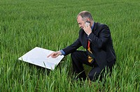 businessman with blueprints and a mobile phone in the field