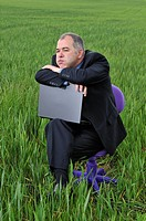businessman bored at a green field with a laptop