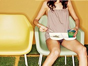 Young woman sitting on plastic chair, eating Asian noodles
