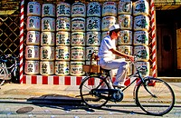 Japan, Kyoto, cyclist and barrels of sake