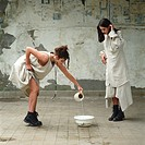Two women, one pouring water into a bowl