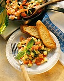 Tomato and courgette ragout on plate with baguette slices