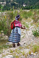 Guatemala, Mayan woman walking on dirt road