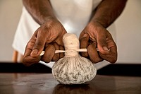 India, Kerala, man tying ayurveda medicine in cloth, close_up