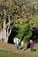 Austria, Salzburg, Flachau, Family walking in autumn meadow