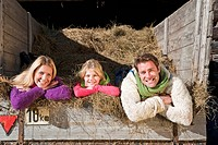 Austria, Salzburg, Flachau, Family lying in hay trailer