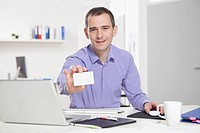 Germany, Bavaria, Munich, Businessman in office holding business card