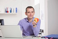 Germany, Bavaria, Munich, Businessman holding apple