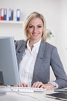 Germany, Bavaria, Munich, Businesswoman using computer in office, smiling, portrait