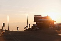 Italy, Trentino_Alto Adige, Alto Adige, Bolzano, Seiser Alm, Mid adult man carrying skis on road in morning