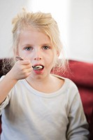 Blond girl eating a spoonful of yoghurt