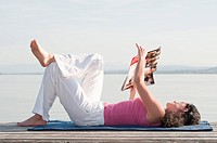 Mid adult woman lying on jetty and reading book