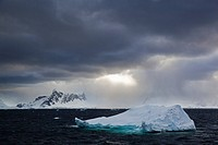 South Atlantic Ocean, Antarctica, Antarctic Peninsula, Gerlache Strait, Iceberg with snow_covered mountain range at dawn