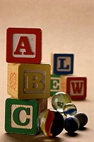 Close_up of alphabet building blocks and marbles