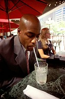 Businessman drinking a beverage with a straw